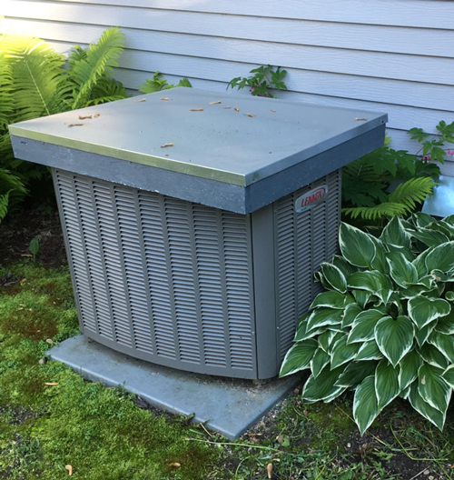 central air conditioning unit in backyard with cover over the top.