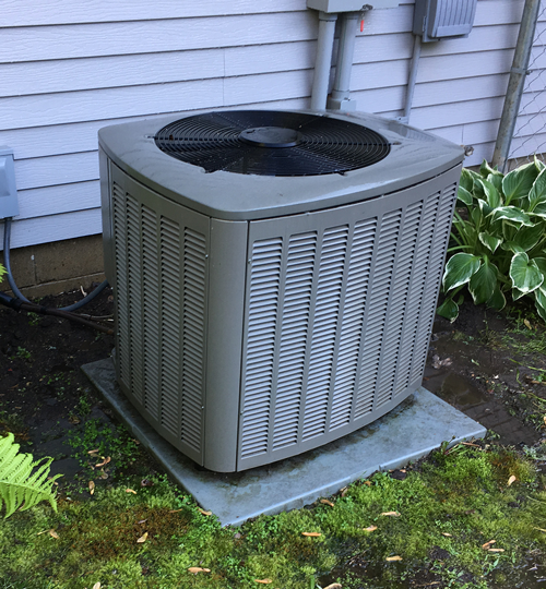 central air conditioning unit in backyard with cover off and bushes cleared around it.