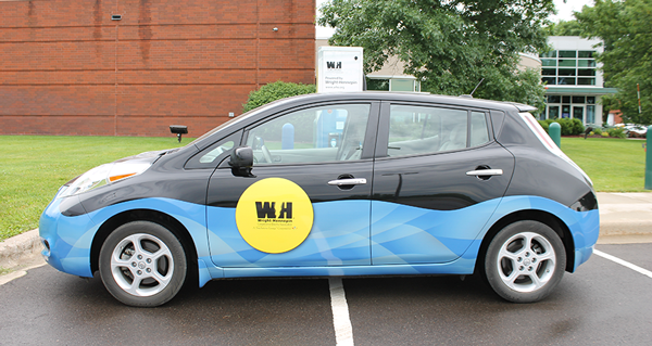 Wright-Hennepin's Nissan Leaf in front of its charger located in Rockford, MN.