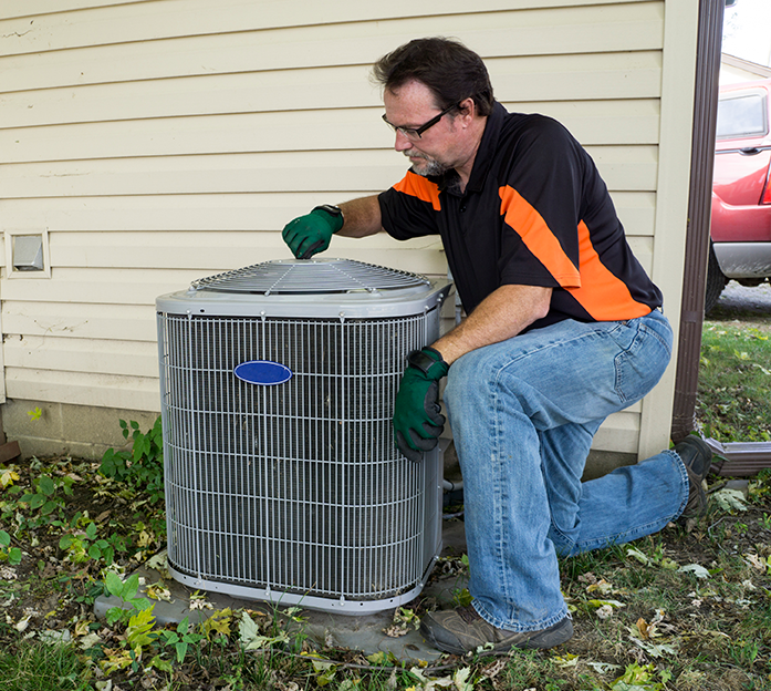 Technician inspecting/maintaining an air conditioner unit.