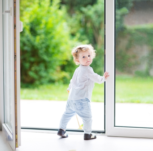 Very young girl going outside while holding open a glass door.