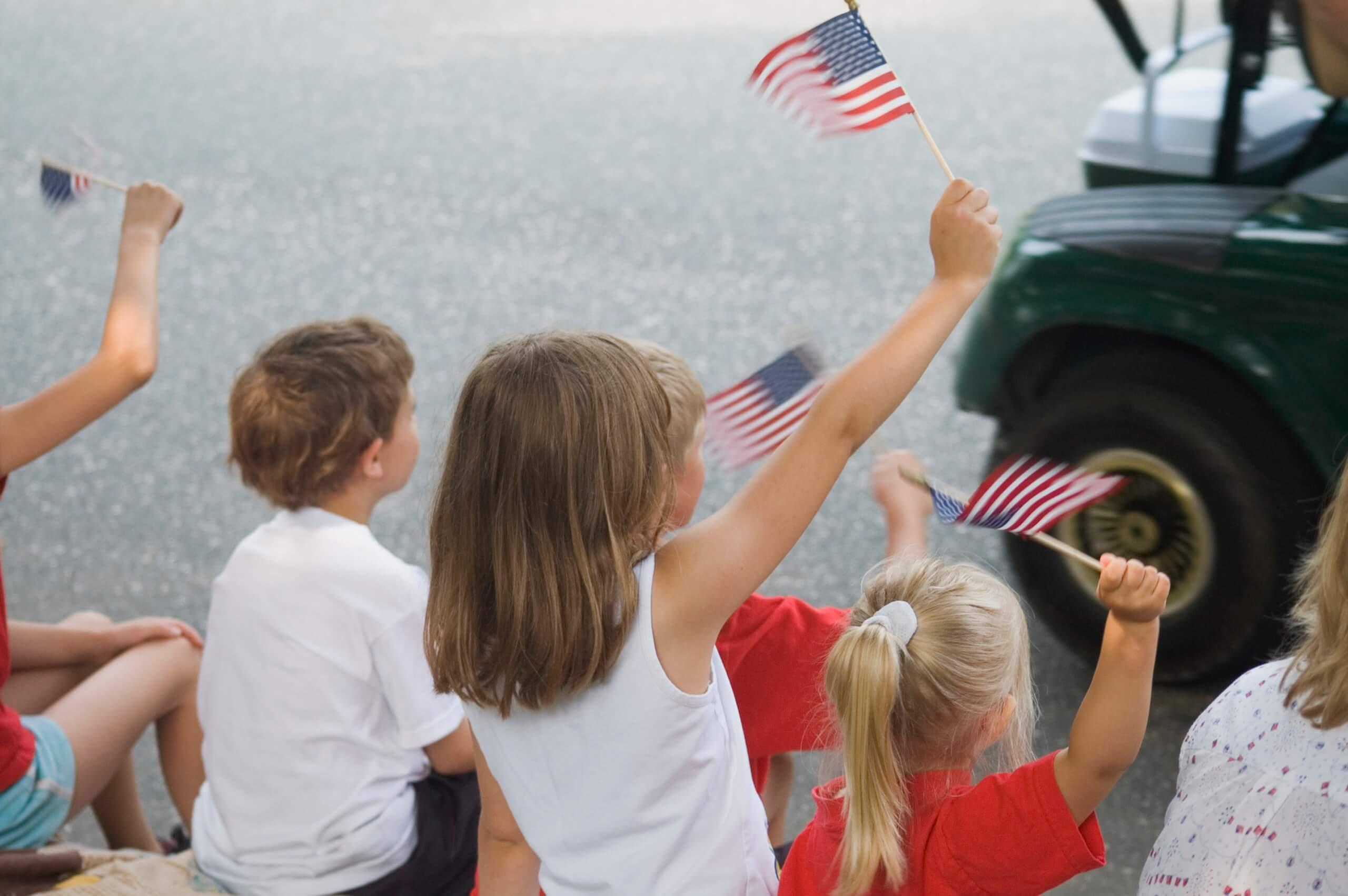Kids wave American flags at a parade that Wright-Hennepin Electric particpated in