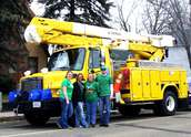 Wright-Hennepin Electric employees stand next to their truck