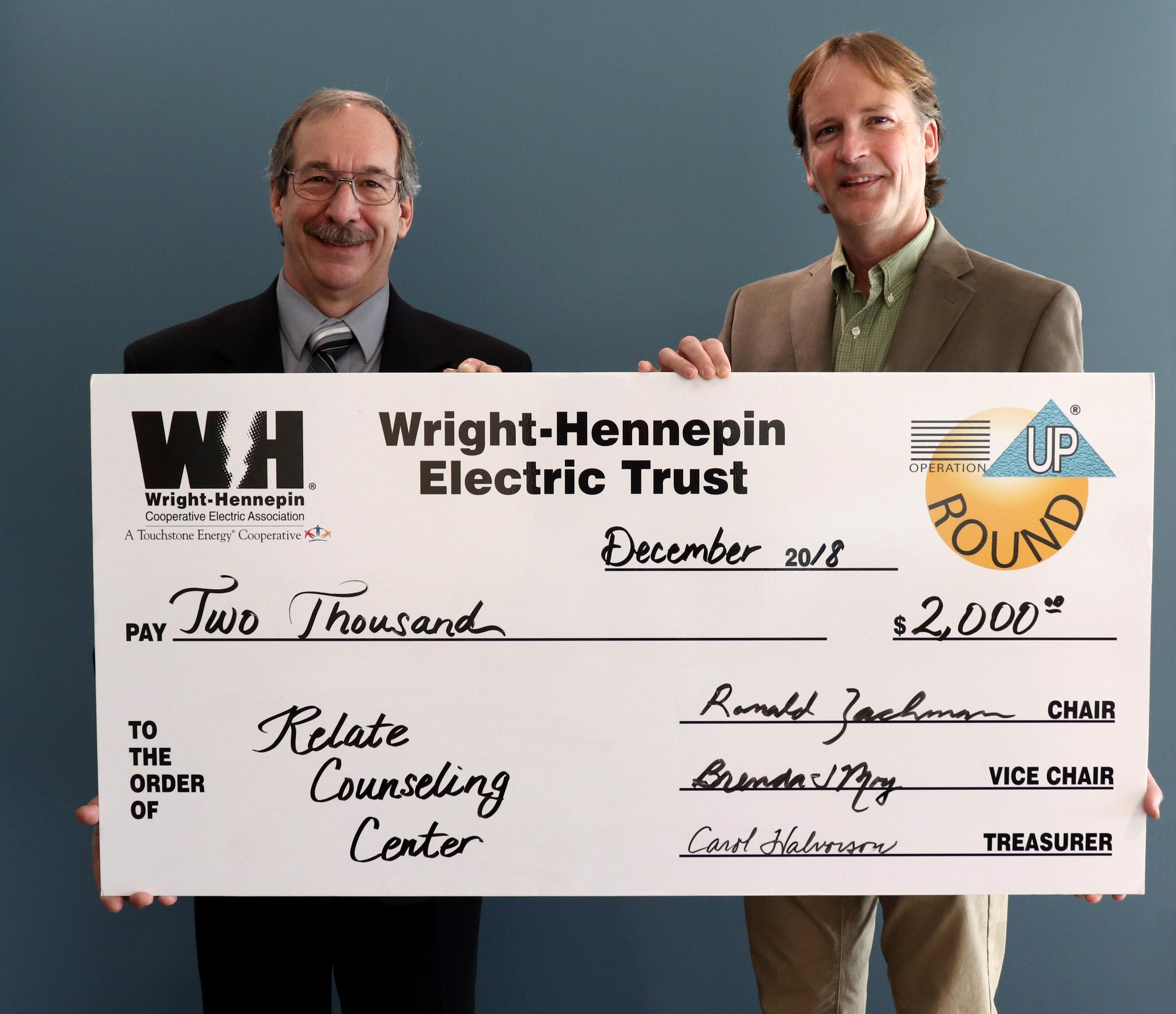 Two people hold up check given to them by Wright-Hennepin Electric
