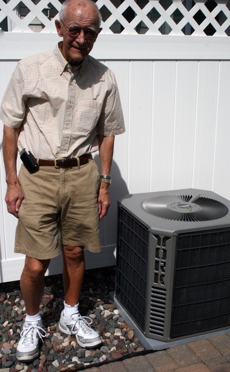 Wright-Hennepin Electric member stands next to his air conditioner