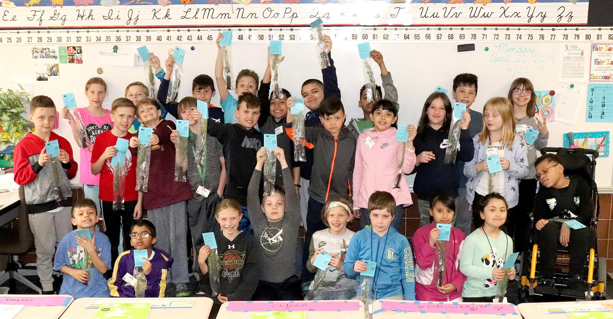 A classroom of students from Northwinds Elementary School in Buffalo hold up their new tree seedlings